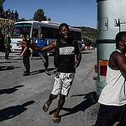 Congolese asylum seekers race toward buses that will take them to the Mytilene ferry port which will take them to Athens from Moria camp. Authorities planned to move 200+ asylum seekers a day after a fatal fire and clashes with police took place at the camp on Lesvos Island in Greece onMonday, September 30, 2019.