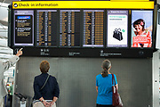 "A departures information board at Heathrow Airport's Terminal 5 is viewed by passengers who stands motionless to read the details of flight departure times to echo that of a Vodafone advertisement containing a tourist on a beach, a generic scene of a person on holiday taking advantage of low mobile phone charges in mainland Europe.  A finger from an unseen traveller points to a flight time and to ladies stand gazing up at the check-in guide that helps tell which is the check-in zone of this 400 metre-long terminal that has the capacity to serve around 30 million passengers a year. From writer Alain de Botton's book project ""A Week at the Airport: A Heathrow Diary"" (2009)."