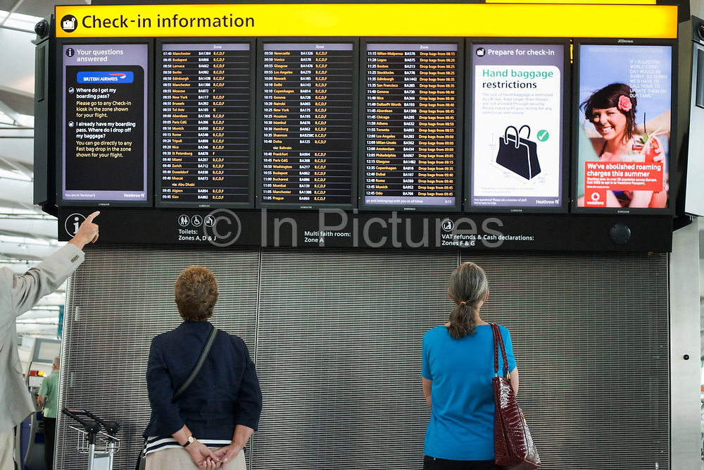 """A departures information board at Heathrow Airport's Terminal 5 is viewed by passengers who stands motionless to read the details of flight departure times to echo that of a Vodafone advertisement containing a tourist on a beach, a generic scene of a person on holiday taking advantage of low mobile phone charges in mainland Europe.  A finger from an unseen traveller points to a flight time and to ladies stand gazing up at the check-in guide that helps tell which is the check-in zone of this 400 metre-long terminal that has the capacity to serve around 30 million passengers a year. From writer Alain de Botton's book project """"A Week at the Airport: A Heathrow Diary"""" (2009)."""