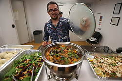 May 24, 2017 - Toronto, ON, Canada - TORONTO, ON- MAY 24  - Amir Abdul Muti Fatal shows off the food as he caters the meal, Muti himself is a refugee.  Guests mingle as Uber hosts a Welcome Refugee Dinner. UNICEF is launching the Welcome Refugee Dinner campaign in Canada. Toronto will play host to the first series of dinners at corporate offices and private homes to bring together refugees and non-refugees to share their life experiences to foster understanding and build communities.  in Toronto. May 24, 2017.  Steve Russell/Toronto Star (Credit Image: © Steve Russell/The Toronto Star via ZUMA Wire)