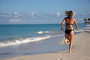 Girl in bikini running away on beach at sunset
