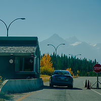 A car enters Banff National Park on Alberta's David Thompson Highway. Forest Fire smoke clouds the air.