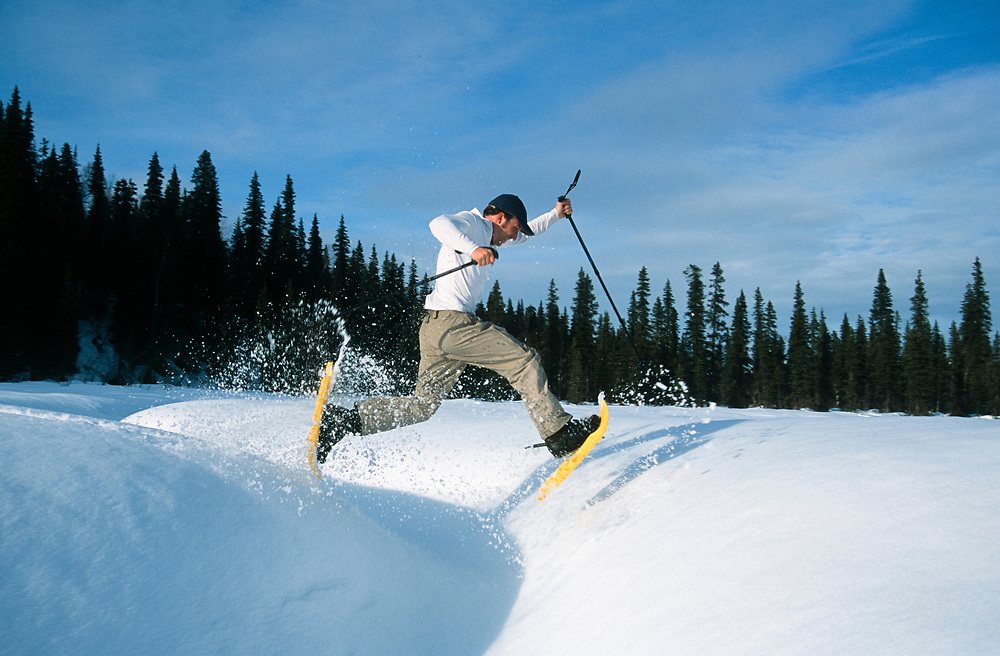 Alaska. Denali State Park. Byers Lake. A snowshoe enthusiast leaps over a hidden stream on a winter day.