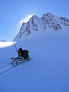 Alaska, Valdez, Thompson Pass.  A snowmachine skier approaches a remote peak via the Deserted Glacier.