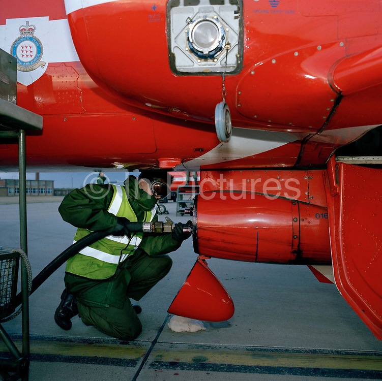 A Dye Team engineer refills the dye-derv mixture to a Hawk jet of the Red Arrows, Britain's RAF aerobatic team. Wearing goggles, military green overalls and fluorescent tabard, a 'line' engineer from the elite 'Red Arrows', Britain's prestigious Royal Air Force aerobatic team, refills the pressurised under-belly smoke pod with a dye-derv mixture that gives the displays the famous coloured smoke of a team Mk 1 Hawk jet aircraft immediately after a winter training flight at the team's headquarters at a damp RAF Scampton, Lincolnshire. The man is a member of the team's support ground crew (called the Blues because of their distinctive blue overalls worn at summer air shows). The team's support ground crew who outnumber the pilots 8:1 and without them, the Red Arrows couldn't fly. Eleven trades are imported from some sixty that the RAF employs and teaches.
