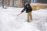 29 DECEMBER 2020 - DES MOINES, IOWA: A worker shovels the snow off the sidewalk in downtown Des Moines during the heaviest snowfall so far of the 2020-21 winter. Des Moines was expected to get about 8 inches of snow before Wednesday morning. Statewide, across Iowa, more than 900 snowplows have been called out to clear the roads.      PHOTO BY JACK KURTZ