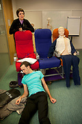 Intense medical session with a tutor / instructor pretending to have a seizure on board a plane for trainees in their first weeks. Virgin Atlantic air stewardess and steward training at The Base training facility in Crawley. Potential hostesses are put through a gruelling 6 week training program, during which they are tested to their limits. With exams every day requiring an 88% score to pass. The Base is a modern environment for a state of the art airline training situated next to Virgin Atlantic's HQ.