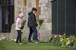 © Licensed to London News Pictures.  11/04/2021. Windsor,UK. Young members of the public place flowers outside Windsor Castle. On Friday the 9th of April Buckingham Palace announced that Prince Philip The Duke of Edinburgh passed away in the morning at Windsor Castle . Photo credit: Marcin Nowak/LNP