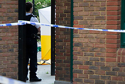 © Licensed to London News Pictures. 10/07/2020. London, UK. Police officers guard a forensics tent at a crime scene near Crossharbour DLR station in Poplar. Police were called shortly after 18:00hrs to reports of two males injured at Alexia Square, E14 close to Crossharbour DLR station. Officers attended and found a man, believed aged in his late teens or early 20s, suffering stab injuries. Emergency services provided first aid but despite their efforts, he was pronounced dead at the scene. A second male, believed aged in his late teens, was taken by the LAS to an east London hospital. Photo credit: George Cracknell Wright/LNP