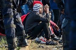 © Licensed to London News Pictures. 25/10/2016. Calais, France.  A young, unaccompanied migrant, hoping to go to the UK, places his hands in a praying motion while waiting to be processed, before leave the migrant camp in Calais, known as the 'Jungle'. French authorities have moved thousands of refugees and migrants living at the makeshift living area on the French coast, with some still refusing to leave. . Photo credit: Ben Cawthra/LNP