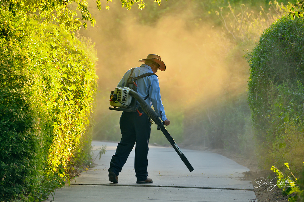 Birding center staff member using a leaf blower on the sidewalk, Edinburgh Scenic Wetlands, Texas, USA