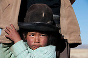 Bolivia 2013. Altiplano. Silvicani. A 4 year old girl clings onto her  father, Cipriano Huchani.