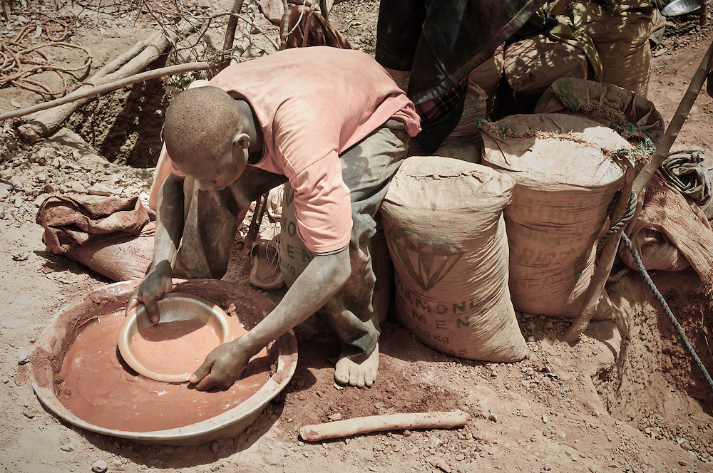 Stock photograph of an African gold miner in Burkina Faso sitting on bags of ore and panning crushed rock to find gold nuggets.