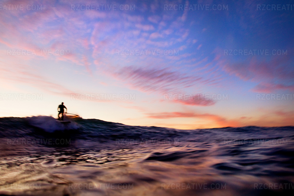 A standup paddleboarder rides a wave at sunset in Orange County, California.