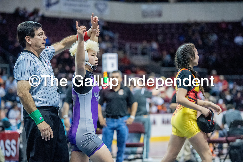 Miyamura Patriot Yele Aycock raises her arm with the Matt referee after winning first place over Centennial Hawk Jaylynn Benitez in the girls121-pound class during the 2018 New Mexico High School Wrestling Championship at the Santa Ana Star Center in Rio Rancho Saturday.