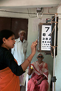 India. Orissa. Village eye camp at Fatak, Sundergarh. September 2012. An ophthalmic assistant tests the vision of a cataract patient.