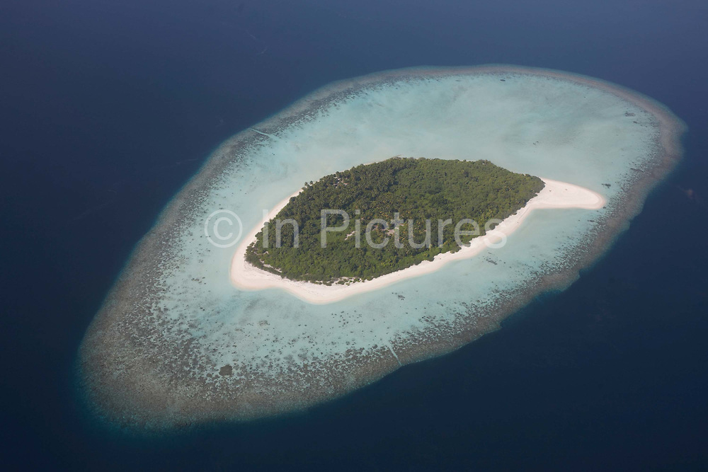 An aerial view of a completely uninhabited, deserted island seen from a regional aircraft passing overhead atolls and islands, an hour's flying time north of Malé, capital of the Indian Ocean Republic of the Maldives. We see the perfectly clear blue sea surrounding a tiny flat island of white coral beach sand, ringing tropical vegetation and scrub that is in jeopardy to rising sea levels as global warming makes sea level locations like this vulnerable to flooding. The Maldives comprise of twenty-six atolls, featuring 1,192 coral islands of which 80 are holiday resorts with 200 inhabited by indigenous communities. This Islamic nation of 298 sq km (115 sq miles), lie seven hundred kilometres (435 miles) south-west of Sri Lanka.