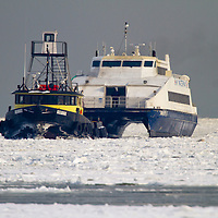 """The Tug Boat """"Reliable"""" escorts the New York Waterway Fast Ferry 'Finest' through a iced over Raritan Bay to it's home port of Belford NJ.   A extended period of sub freezing temperatures iced over much of New York Harbor creating issues for commuter ferries and commercial marine traffic."""