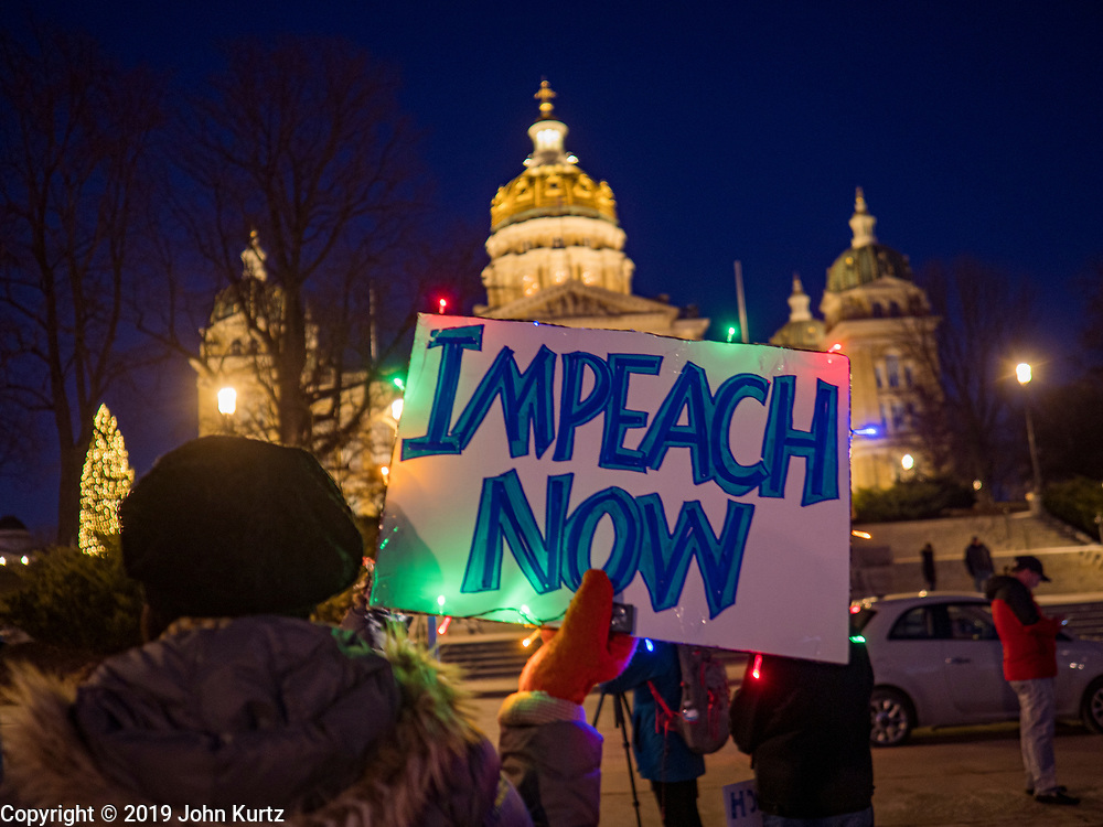 17 DECEMBER 2019 - DES MOINES, IOWA: JENNIFER NELLANS, from Des Moines, carried a sign decorated with Christmas lights during a protest calling for President Donald Trump's impeachment. About 300 people came to the Iowa State Capitol in Des Moines in near freezing weather Tuesday evening to call for Trump's impeachment. The rally, and others like it around the US, come on the eve of an impeachment vote in the US House of Representatives.     PHOTO BY JACK KURTZ
