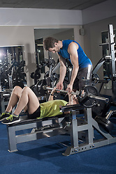 Mid adult woman lifting weight with help of spotter, Bavaria, Germany