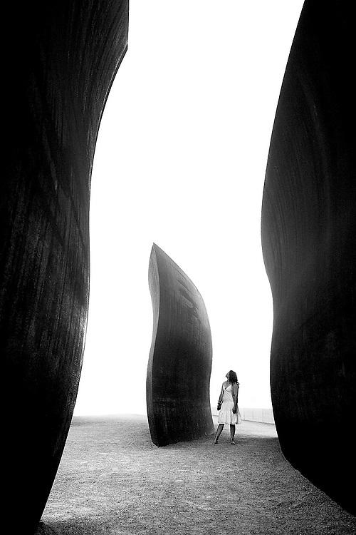 "Emma Jubinski walks among the fins of Richard Serra's ""Wake"" at the Seattle Art Museum Olympic Sculpture Park in Seattle, Washington."