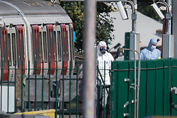 © Licensed to London News Pictures. 15/09/2017. London, UK. Forensics officers, one is a gas mask (L) can be seen next to the evacuated tube train at Parsons Green Station after a small explosion during the morning rush hour. A number of casualties have been reported. Photo credit: Peter Macdiarmid/LNP