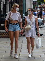 © Licensed to London News Pictures. 23/07/2020. London, UK. Two young shoppers in Chelsea wear masks while shopping on the Kings Road before it becomes compulsory in shops in England tomorrow. Face masks will be compulsory in shops, takeaway cafes and supermarkets from 24th July and enforced by the Police, with anyone who fails to wear one liable to a £100 fine. Photo credit: Alex Lentati/LNP