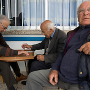 Men play backgammon in the Greek coffee shop in the village of Pyla in the Larnaca District of Cyprus March 11, 2014.  It is one of only four villages located within the United Nations Buffer Zone and is a mixed community with both Greek and Turkish Cypriots living side by side. This year marks 40 years since the Cyprus National Guard staged a coup in Cyprus and the subsequent Turkish military intervention, which escalated a civil war between the Greek and Turkish Cypriot communities on the island. After the ceasefire a heavily restricted UN controlled Buffer Zone between the north and south of the island was put into operation. It stretches 180 Km across the whole island measuring 7.4 km at its widest and 3.3 meters at its narrowest point. It is restricted to the general public and no Greek or Turkish Cypriots are allowed inside. REUTERS/Neil Hall (BRITAIN)