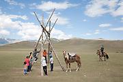 Children play on a swing at a Kyrgyz horse games festival. Bosogo jailoo, Naryn province, Kyrgyzstan.