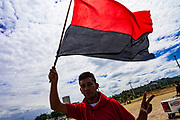 """10 JANUARY 2007 - MANAGUA, NICARAGUA: A Sandanista supporter waves the red and black Sandanista banner in Managua. Daniel Ortega, the leader of the Sandanista Front, was sworn in as the President of Nicaragua Wednesday. Ortega and the Sandanistas ruled Nicaragua from their victory of """"Tacho"""" Somoza in 1979 until their defeat by Violetta Chamorro in the 1990 election.  Photo by Jack Kurtz"""