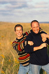 Two men in sweaters standing in tall grass in East Hampton,NY