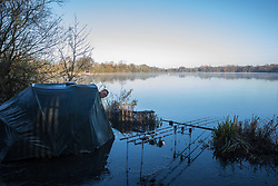 Harefield, UK. 19 January, 2020. A fisherman checks his fishing rods as early morning mist lies across a lake in Colne Valley Regional Park across which a 3.4 km-long viaduct would be constructed should plans for the HS2 high-speed rail link be approved.