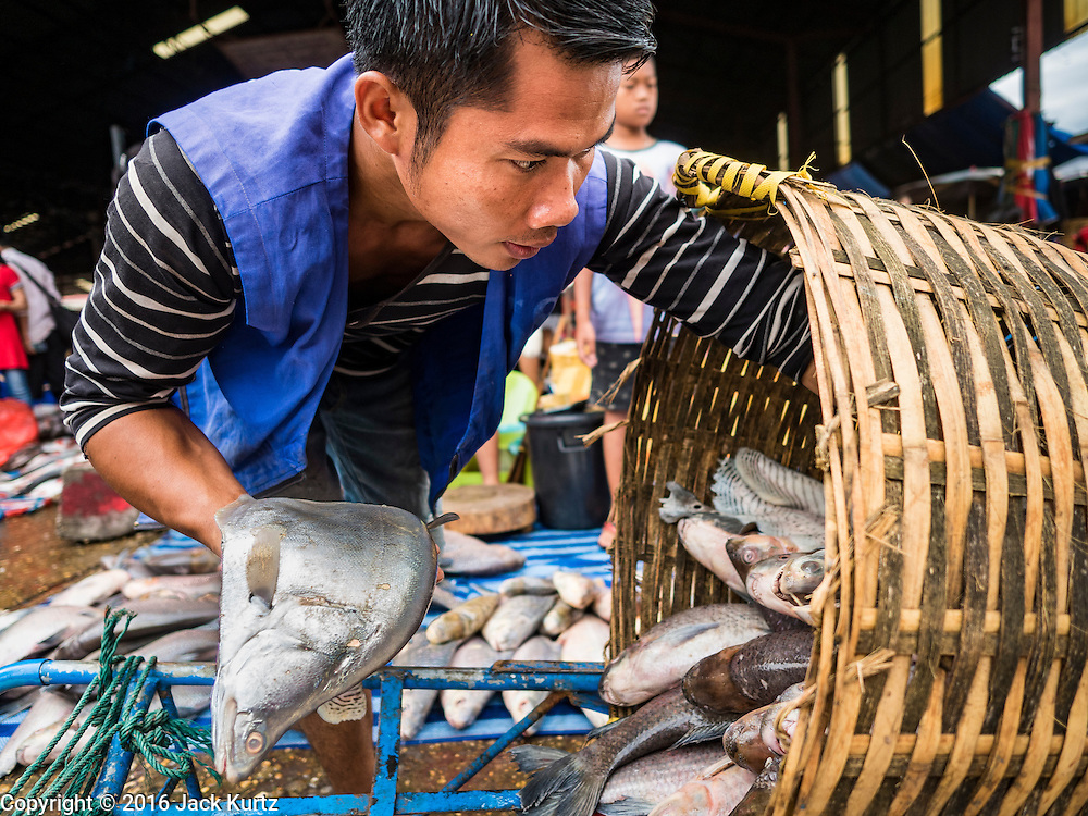 16 JUNE 2016 - PAKSE, CHAMPASAK, LAOS: A porter delivers fresh fish to a fishmonger in Dao Heuang Market, the largest market in Pakse. Pakse is the capital of Champasak province in southern Laos. It sits at the confluence of the Xe Don and Mekong Rivers. It's the gateway city to 4,000 Islands, near the border of Cambodia and the coffee growing highlands of southern Laos.      PHOTO BY JACK KURTZ