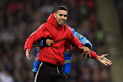 Staff escort a pitch invader off the pitch near England's Wayne Rooney (not pictured) during the International Friendly at Wembley Stadium, London.