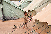 Tunisia 2011. Remada camp for refugees from Libya. Child playing on guy ropes.
