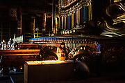 Lighting candles in Migjid Janraisig Sum<br /> Gandantegchinlen Monastery<br /> Ulaanbaatar<br /> Mongolia