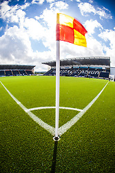 An upright image of the corner flag in sunlight, with the main stand behind. The Falkirk Stadium, with the new pitch work for the Scottish Championship game v Morton. The woven GreenFields MX synthetic turf and the surface has been specifically designed for football with 50mm tufts compared with the longer 65mm which has been used for mixed football and rugby uses.  It is fully FFA two star compliant and conforms to rules laid out by the SPL and SFL.<br /> ©Michael Schofield.