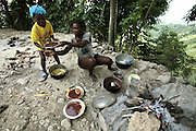A woman hands her son a plate with maise (corn paste) with a bean broth over it as dinner time begins high on the mountain above Carrefour, Haiti.  With no money, the meals are usually the same on tha daiy basis, and malnutrition is always close at hand.