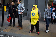 Woman dressed up as a banana crossing the road in central London, UK.