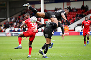 Barnsley defender Dimitri Cavare (12) and Barnsley forward Jacob Brown (33) get tangled up during the EFL Sky Bet League 1 match between Walsall and Barnsley at the Banks's Stadium, Walsall, England on 23 March 2019.