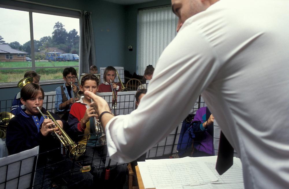 Teacher conducting musicians in school UK