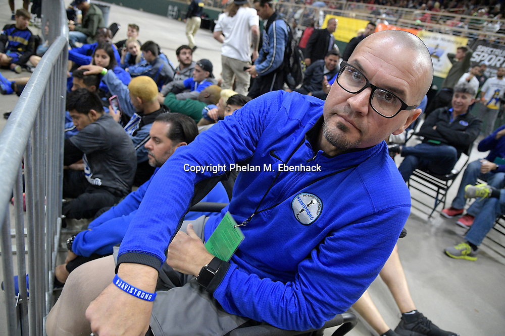 South Dade principal Javier Perez shows his wrist band while watching one of the school's championship matches during the FHSAA State Wrestling Finals, Saturday, March 4, 2017, in Kissimmee, Fla. (Photo by Phelan M. Ebenhack)