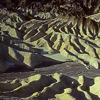 Morning light glows on eroded mineral hills below Zabriskie Point in California's Death Valley National Park.