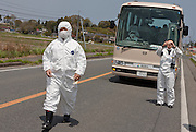 Government officials from Minami Soma dressed in nuclear protection suits pass the police roadblock set up to reinforce the nuclear contamination area 20 kilometres from the tsunami damaged Fukushima Daichi nuclear power station, to visit the affected area. Near Minami Soma, Fukushima, Japan. Wednesday May 4th 2011