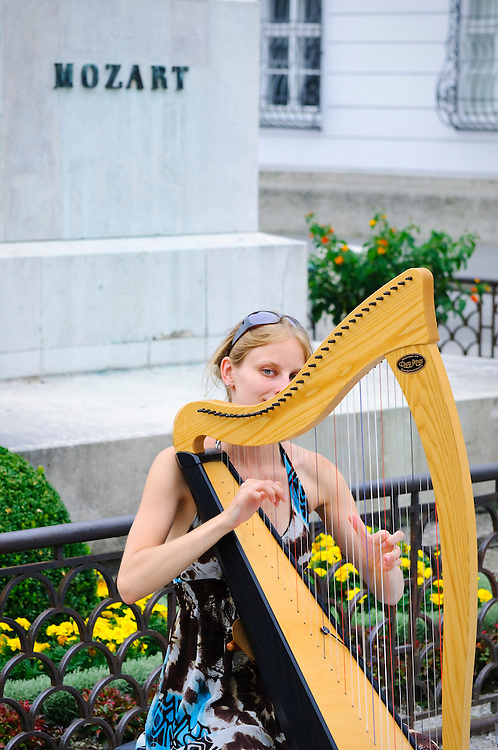 A female harpist plays a harp in front of a statue of Mozart on a summer evening in Salzburg, Austria. Salzburg was the birthplace of Mozart, among other fine musicians. (Salzburg, Austria - July 22, 2010)