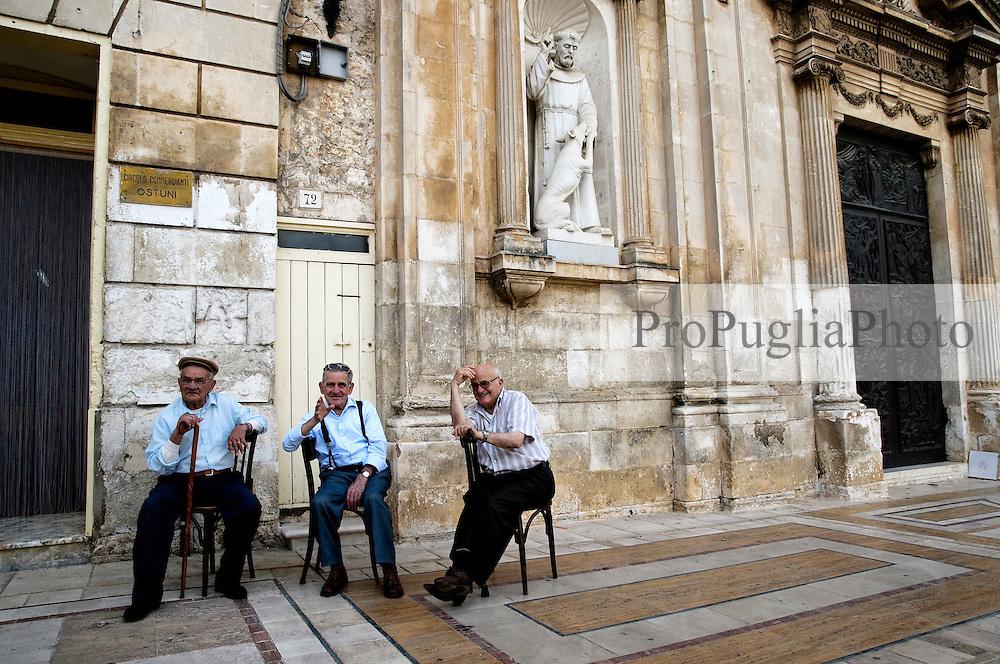 Tre uomini anziani son seduti davanti alla sede del circolo dei commercianti, sulla piazza del comune di Ostuni, e chiacchierano tra loro.