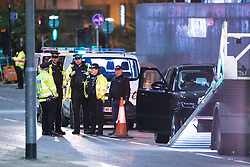 © Licensed to London News Pictures. 30/10/2019. Manchester, UK. Police close off Deansgate and a part of Chester Road and surround a black Range Rover before towing it away on a low loading truck . Greater Manchester Police report that two men were arrested nearby after the Range Rover was stopped on Deansgate. The two men remain in custody for questioning on suspicion of the commission, preparation or instigation of acts of terrorism.  Photo credit: Joel Goodman/LNP