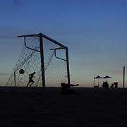 A runner jogs past a football match at sunset on Copcabana beach, Rio de Janeiro,  Brazil. 5th July 2010. Photo Tim Clayton..