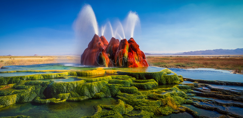 The continuous Fly Geyser of Fly Ranch is on private land in Nevada and began during 1916 when a water well drilling operation accidentally penetrated a geothermal source.<br /> Fly Geyser, also known as Fly Ranch Geyser is a small geothermal geyser that is located approximately 20 miles (32 km) north of Gerlach, in Washoe County, Nevada. The Geyser is located in Hualapai Flat, about 1/3 of a mile from State Route 34. It is large enough to be seen from the road.<br /> .....<br /> Fly Geyser is a little-known tourist attraction, even to Nevada residents. It is located near the edge of Fly Reservoir and is only about 5 feet (1.5 m) high, (12 feet (3.7 m) counting the mound on which it sits). The water well functioned normally for several decades, but in the 1960s geothermally heated water found a weak spot in the wall and began escaping to the surface. Dissolved minerals started rising and accumulating, creating the mount on which the geyser sits, which continues growing. Today water is constantly spewing, reaching 5 feet (1.5 m) in the air. The geyser contains several terraces discharging water into 30 to 40 pools over an area of 30 hectares (74 acres). The geyser is made up of a series of different minerals, which gives it its magnificent coloration.<br /> .....<br /> There are two additional geysers in the area that were created in a way similar to Fly Geyser. The first geyser is approximately three feet high and is shaped like a miniature volcano. The second geyser is cone-shaped and is of the same approximate size as Fly Geyser. Like Fly Geyser, these geysers are continually growing.