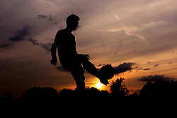A silhouette of a man passing a football